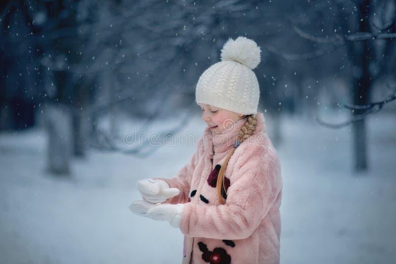 Dziewczyna bawić się w śnieżnym parku fotografia royalty free
