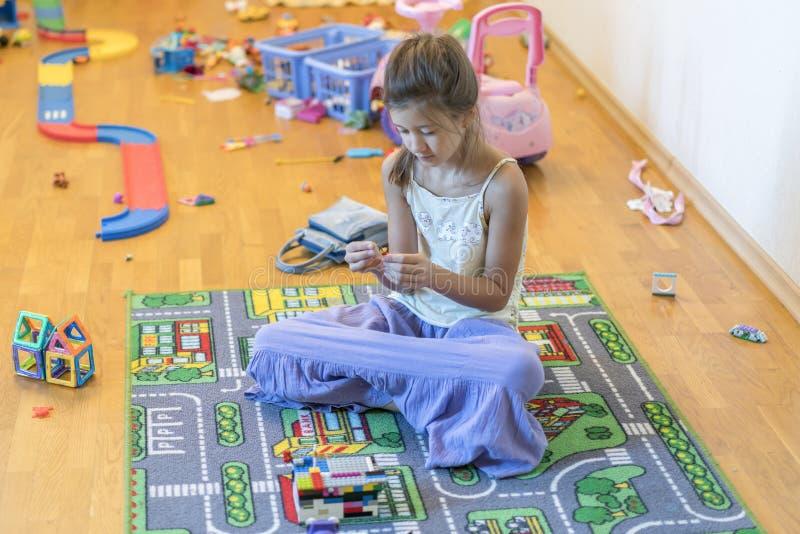 Dziewczyna bawić się w pokoju dziewczyny 8 lat na podłoga z zabawkami obrazy royalty free