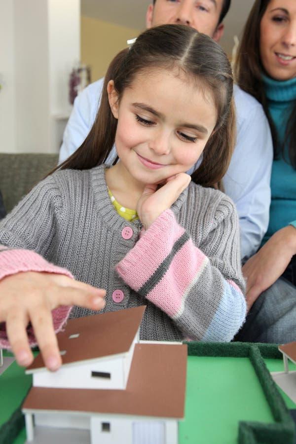 Dziewczyna bawić się z modela domem fotografia stock