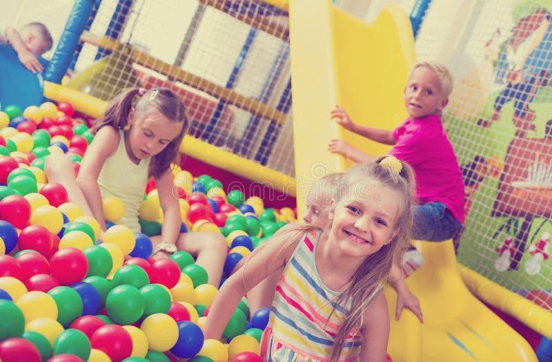 Dziewczyna bawić się z stubarwnymi plastikowymi piłkami zdjęcie royalty free