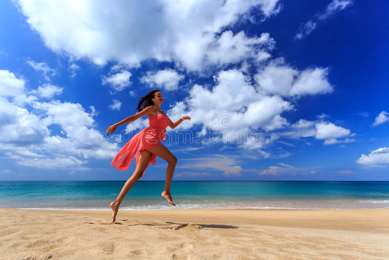 Dziewczyna bieg na plaży i doskakiwanie fotografia stock