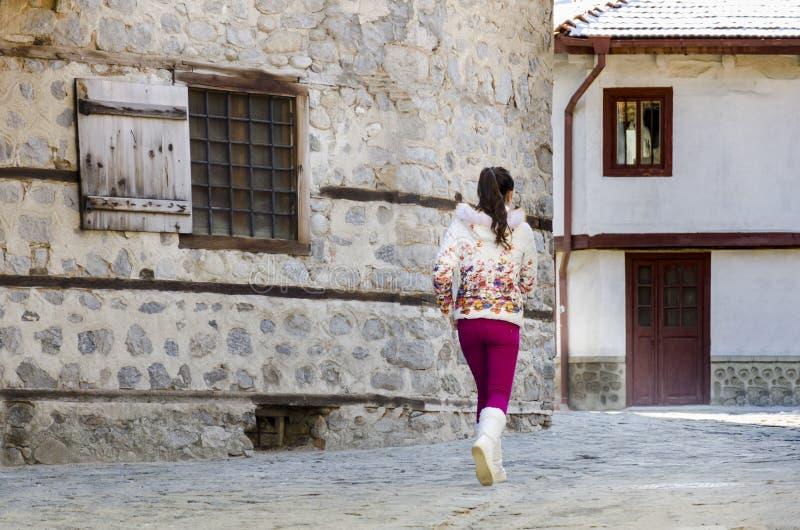 Dziewczyna bieg na starym kamieniu brukował ulicę z tradycyjnymi domami obrazy royalty free