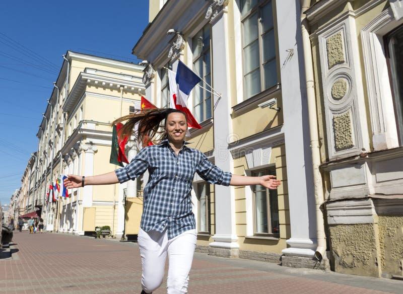 Dziewczyna bieg puszek ulica na słonecznym dniu z jego wręcza outst zdjęcie royalty free