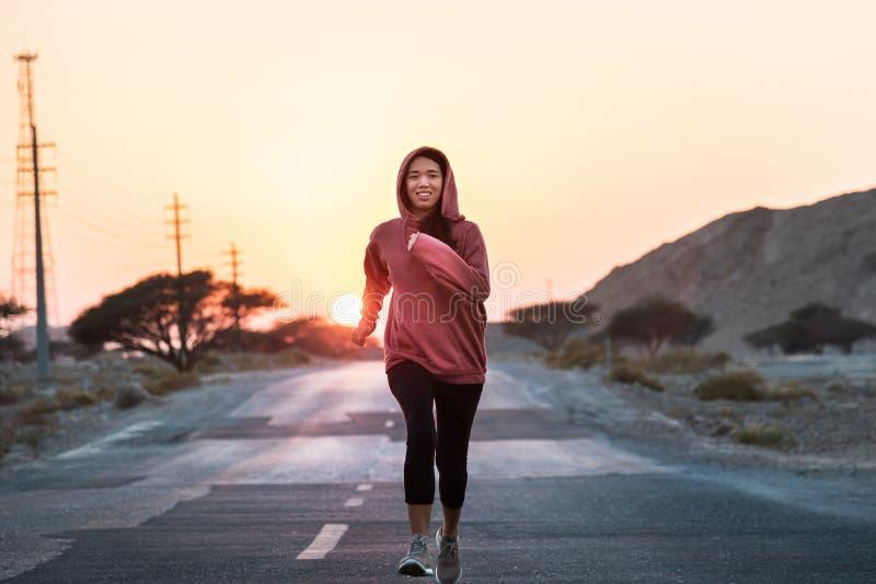 Dziewczyna bieg w zmierzchu jest ubranym różowy hoody obraz royalty free