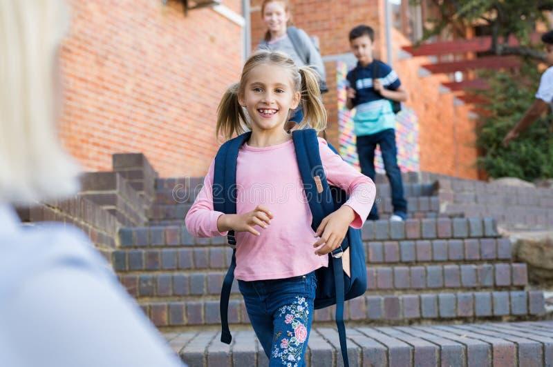 Dziewczyna biega jej mama po szkoły fotografia stock