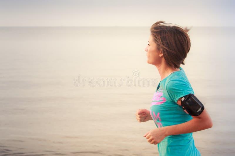 dziewczyna biega na plaży przy niskim przypływem obrazy stock