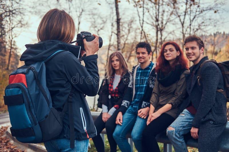 Dziewczyna bierze fotografię jej przyjaciele Grupa młodzi przyjaciele siedzi na poręczówce blisko drogi fotografia stock