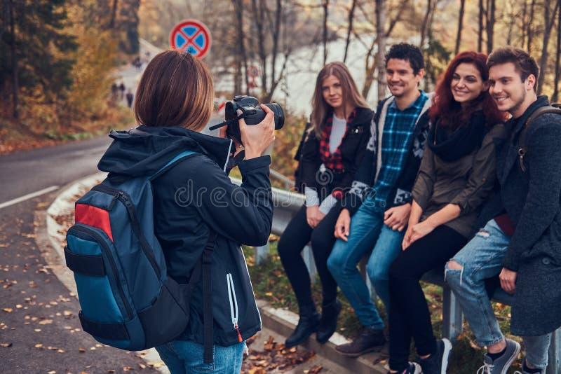 Dziewczyna bierze fotografię jej przyjaciele Grupa młodzi przyjaciele siedzi na poręczówce blisko drogi obrazy stock