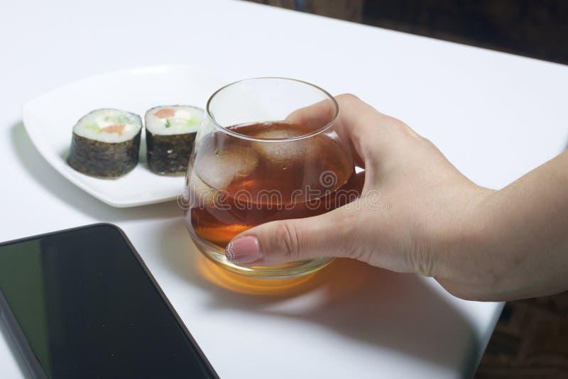 Dziewczyna bierze szkło whisky od stołu z lodem W pobliżu jest talerz suszi i smartphone Odpoczynek dzień wolny zdjęcie royalty free