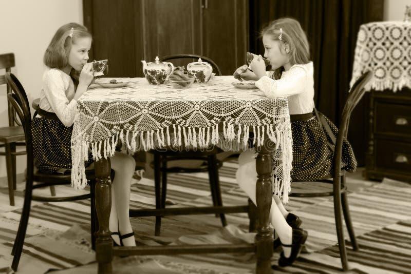 Dziewczyna bliźniacy pije herbaty przy antyka stołem z koronkowym tablecl zdjęcie stock