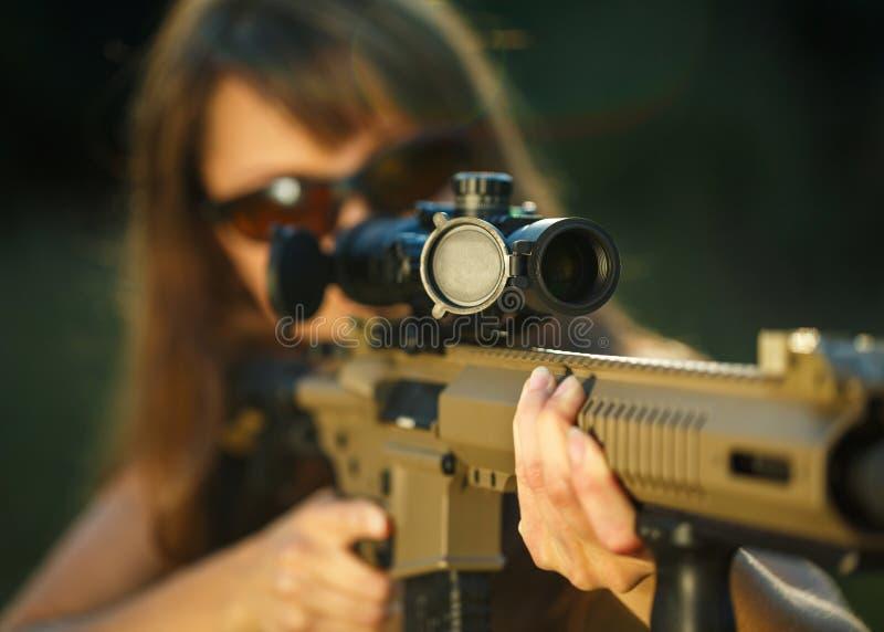Dziewczyna celuje przy z pistoletem dla oklepiec strzelaniny i strzelanin szkieł zdjęcia royalty free