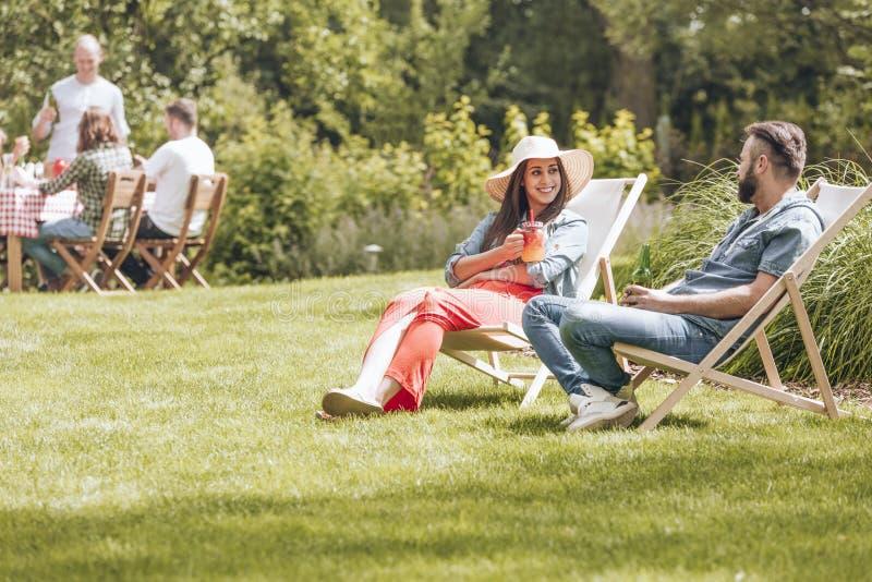 Dziewczyna, chłopiec obsiadanie na deckchairs i flirtować podczas póżniej zdjęcia stock