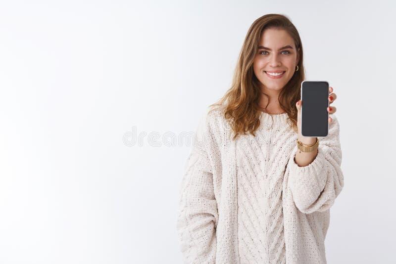 Dziewczyna chce słuchać twój opinię pokazywać ci smartphone pokazu Atrakcyjnej powabnej przyglądającej kobiety przedłużyć ręka zdjęcie stock