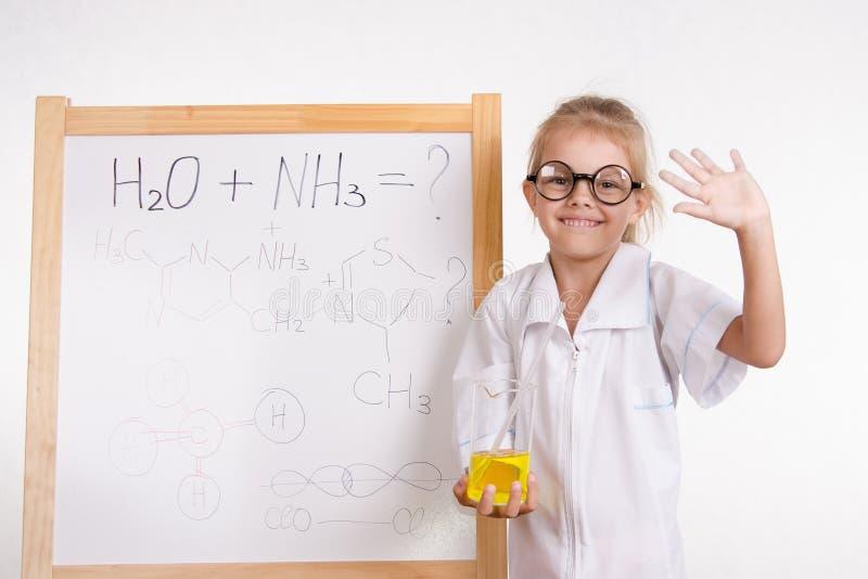 Dziewczyna chemika kolba przy deską z inskrypcją obraz stock