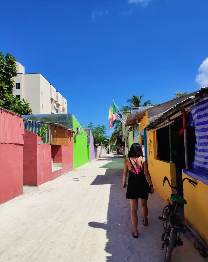 Dziewczyna chodzi blisko kolorowymi domami w Maldive zdjęcie royalty free