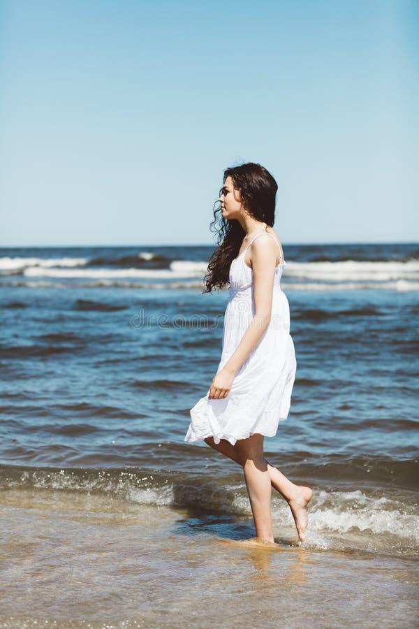 Dziewczyna chodzi przy ocean w biel sukni fotografia stock