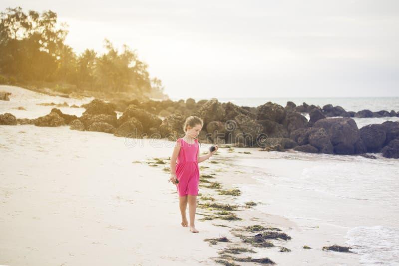 Dziewczyna chodzi samotnie wzdłuż brzeg ocean indyjski i zbiera zdjęcie stock
