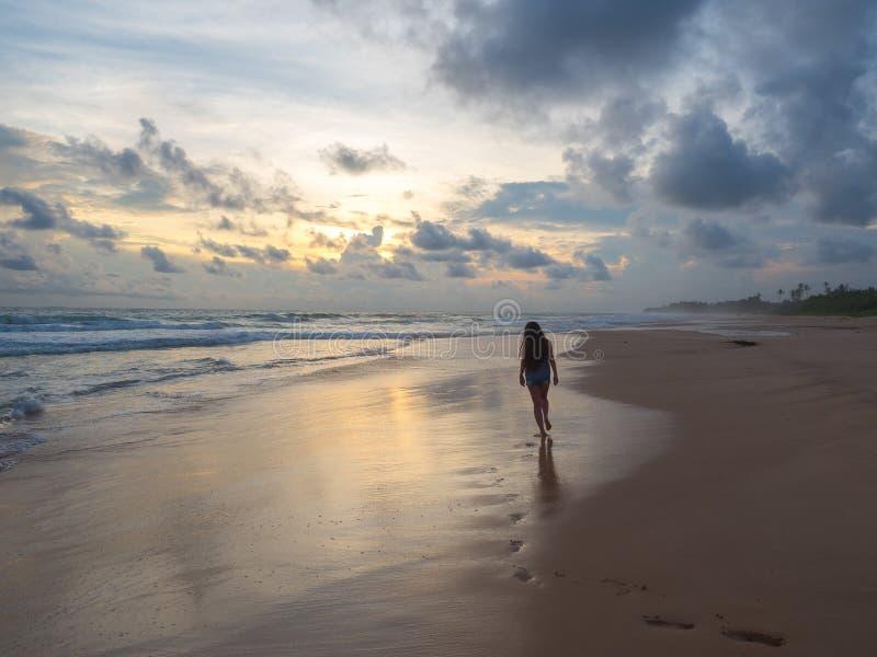 Dziewczyna chodzi wzdłuż plaży przy zmierzchem obrazy stock