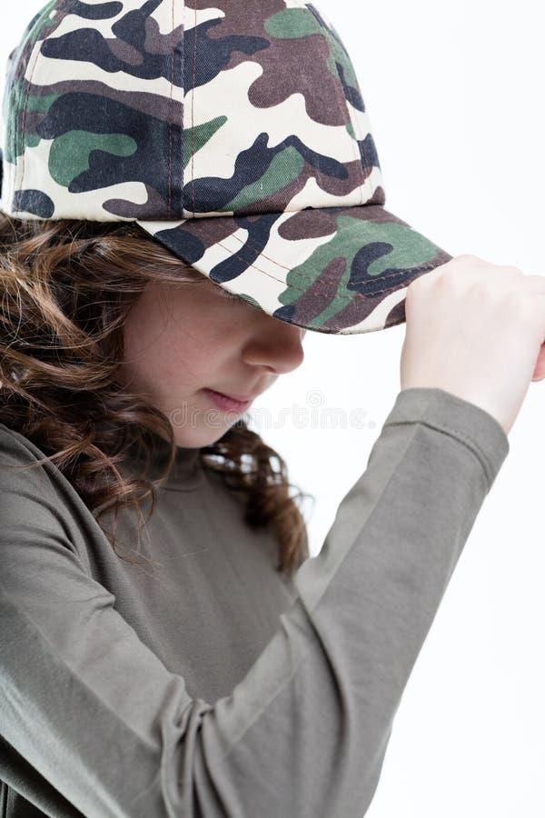 Dziewczyna chuje jej twarz za jej nakrętka szczytem fotografia royalty free