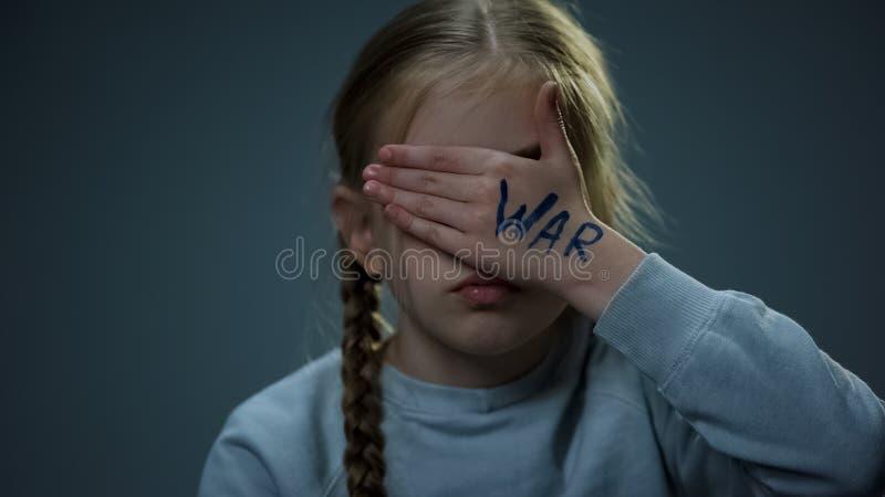 Dziewczyna chuje za r?k? z wojenn? inskrypcj?, mie? nadziej? dla pokoju i bezpiecze?stwa zdjęcie stock