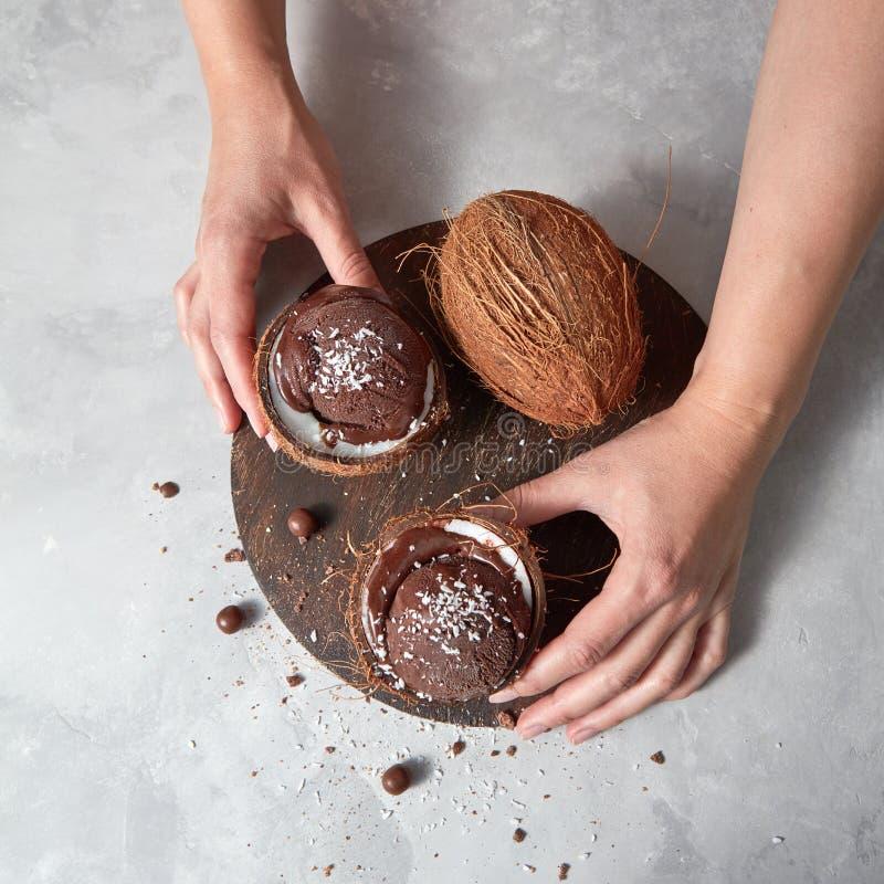 Dziewczyna chwyta dwa halfs koks z czekoladowym sorbet z koks układami scalonymi i czekoladowymi piłkami na drewnianej desce na a zdjęcia stock