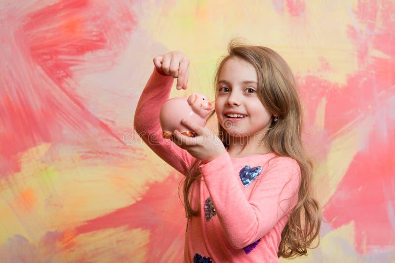 Dziewczyna chwyta moneybox lub prosiątko bank dla savings zdjęcia royalty free