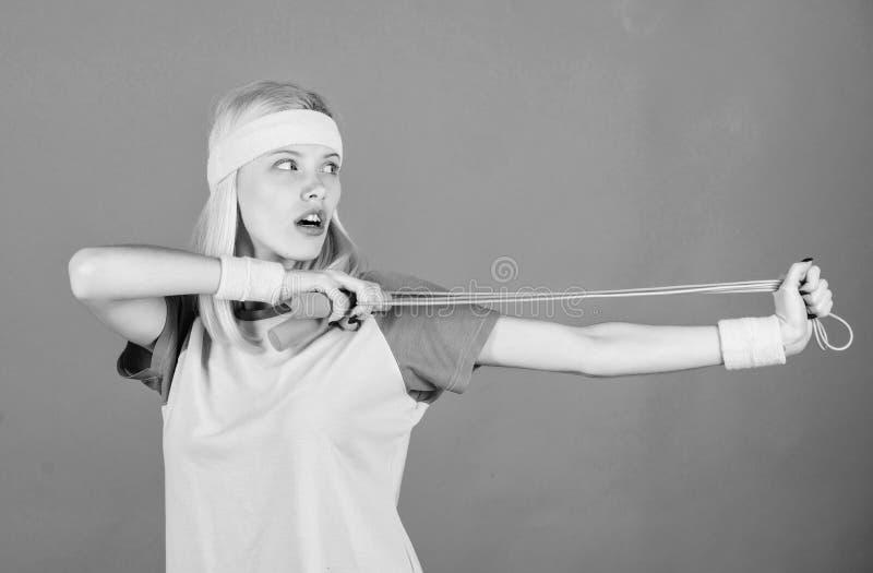 Dziewczyna chwyta skokowej arkany odzieży jaskrawi wristbands Kobieta ćwiczy z skokową arkaną Skokowy wyzwanie tydzień odosobnion fotografia royalty free