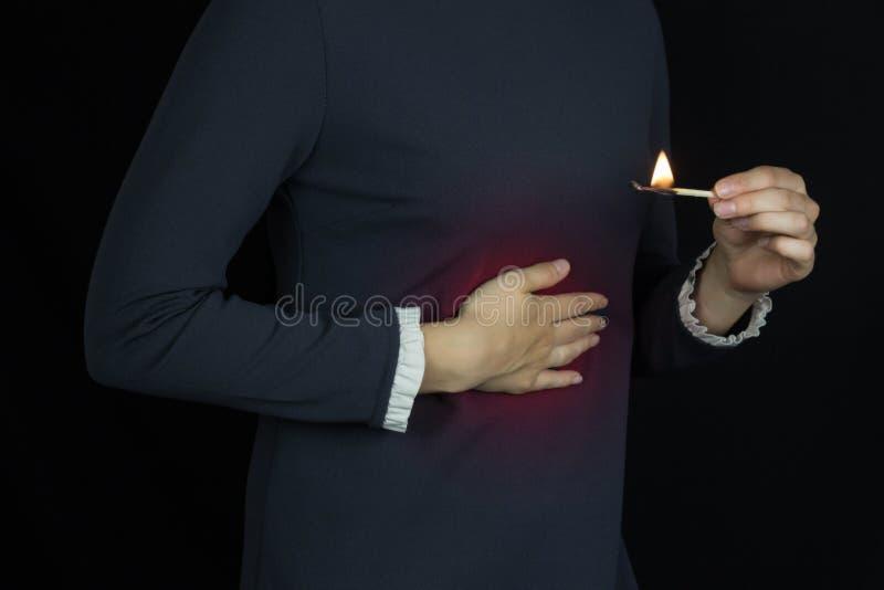 Dziewczyna chwyty dalej żołądek, zgaga w jej żołądku, ogień i palenie w żołądku, fotografia stock