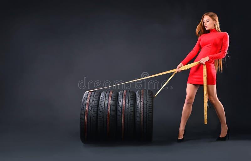 Dziewczyna ciągnie wiązkę nowe opony zdjęcia stock