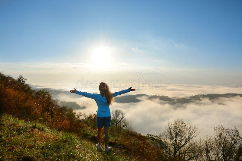 Dziewczyna cieszy się piękną halną scenerię na mgłowym ranku fotografia stock