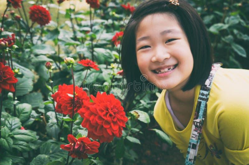 dziewczyna cieszy się pięknej czerwonej dalii zdjęcia stock