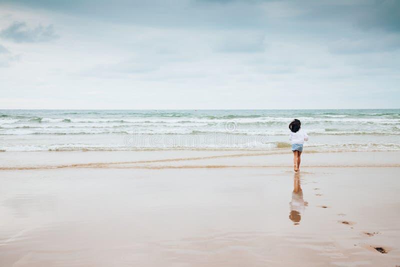Dziewczyna cieszy się plażę z złą pogodą zdjęcia stock