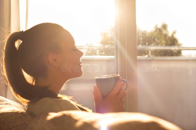 Dziewczyna cieszy się ranek kawę w żywym pokoju obraz stock