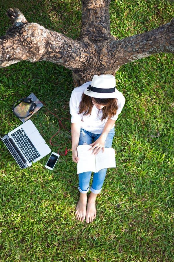 Dziewczyna cieszy się słuchającą muzykę i czytanie sztuka laptop na trawy polu park i książka zdjęcia royalty free