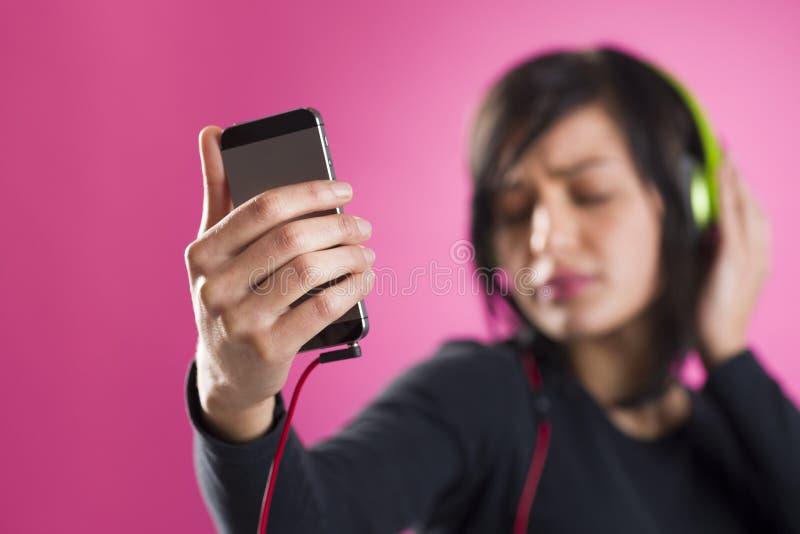 Dziewczyna cieszy się słuchającą muzykę z hełmofonami i odtwarzacz mp3 obraz royalty free