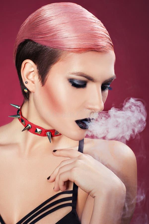 Dziewczyna ciosów dym. obrazy stock