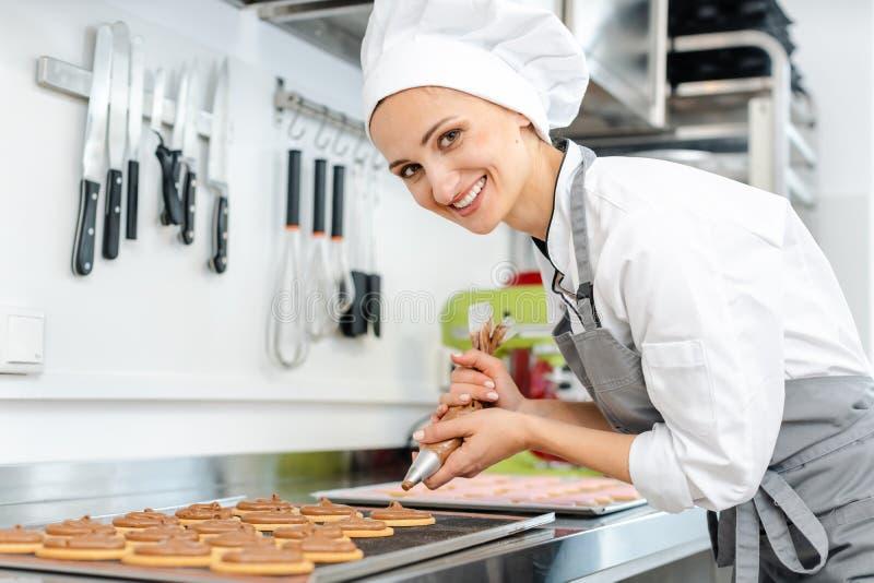 Dziewczyna cukierniczka używająca worka z ciastkami do umieszczania śmietany na ciastkach fotografia stock