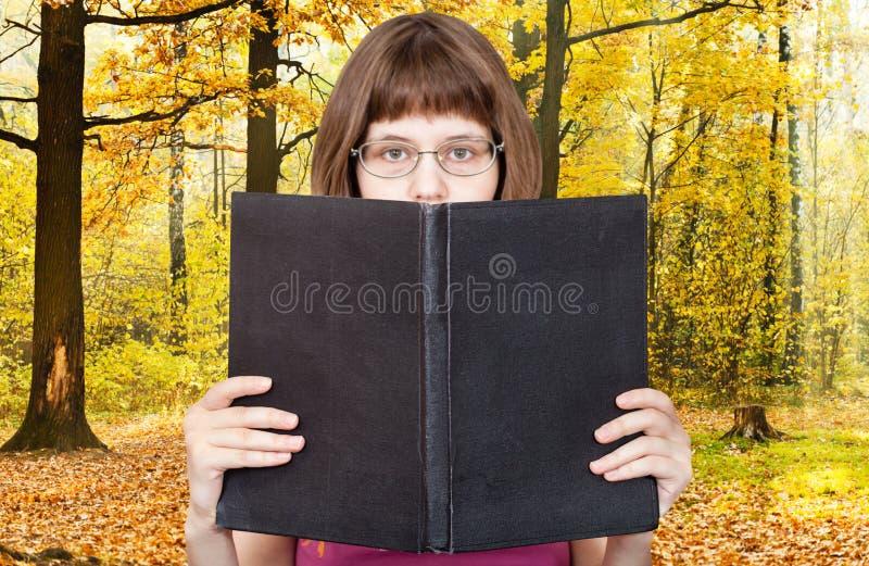 Dziewczyna czyta dużych książki i jesieni drewna zdjęcie stock