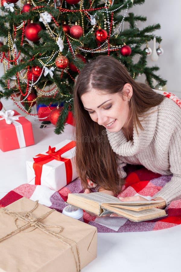 Dziewczyna czyta książkę blisko choinek bożych narodzeń prezentów zdjęcia royalty free