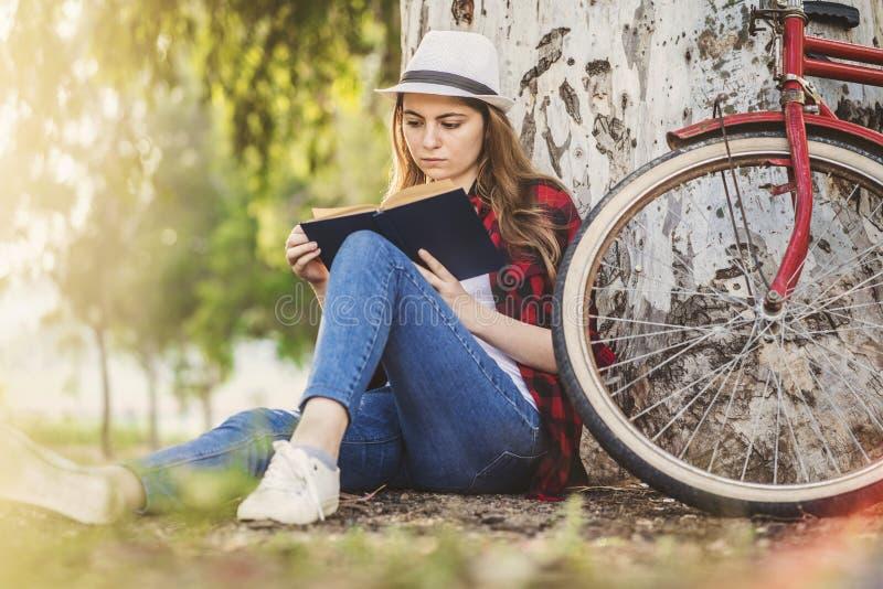 Dziewczyna czyta książkę opiera przeciw drzewu zdjęcie royalty free