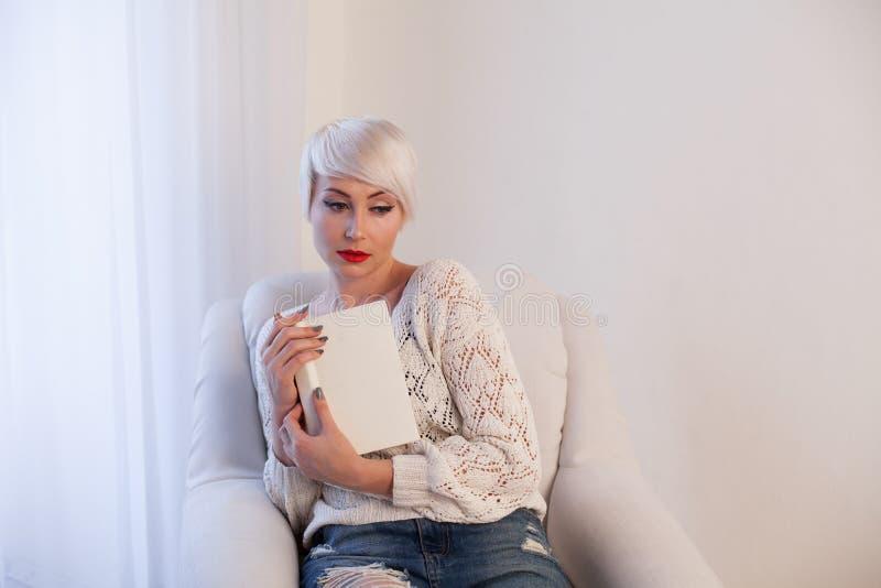 Dziewczyna czyta książkę w białym karle obraz stock