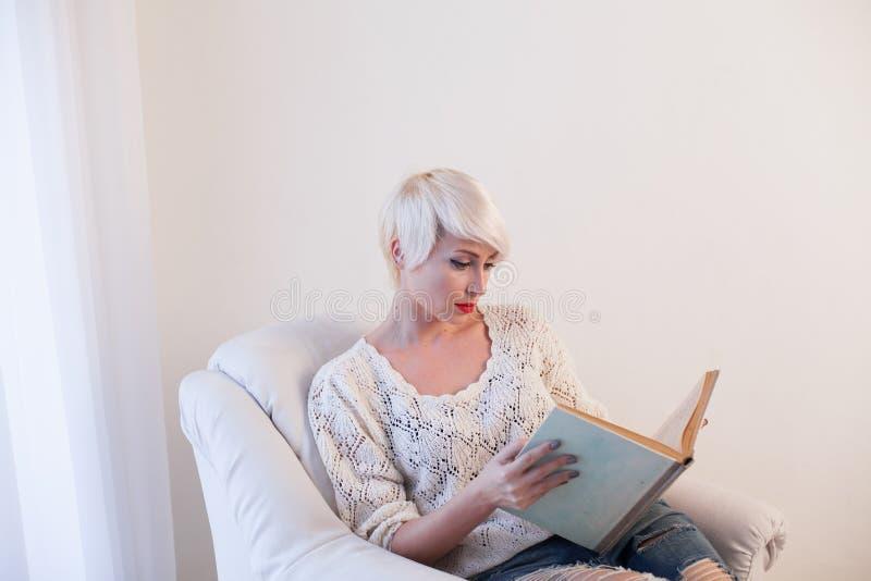 Dziewczyna czyta książkę w białym karle zdjęcia stock