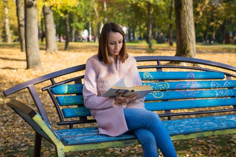 Dziewczyna czyta książkę w jesień parku zdjęcie royalty free