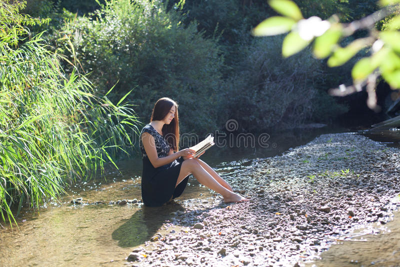 Dziewczyna czyta książkę w lesie zdjęcia stock