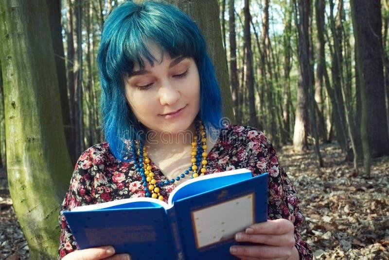 Dziewczyna czyta książkę w lesie zdjęcie royalty free