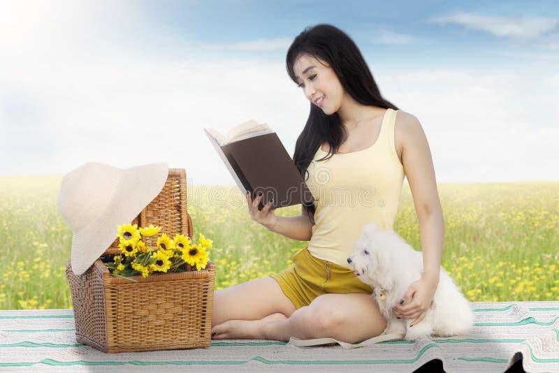 Dziewczyna czyta książkę z psem przy polem obraz royalty free