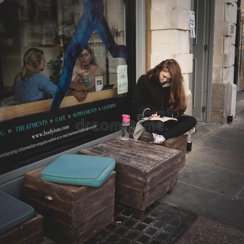 Dziewczyna czyta książkowego na zewnątrz cafè w Notting wzgórzu london uk Marzec 2017 Ciosowy format obrazy stock