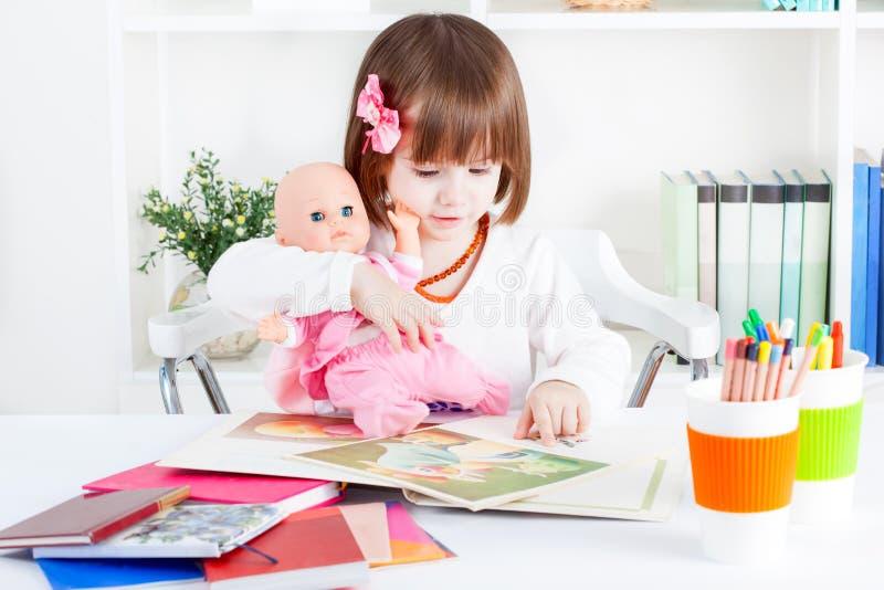 Dziewczyna czyta obrazek książkę dziecko - lala zdjęcie royalty free