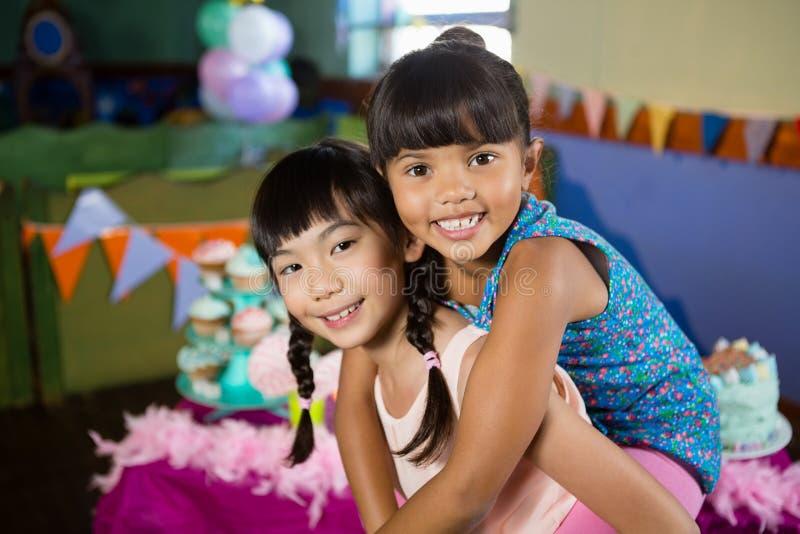 Dziewczyna daje piggyback przejażdżce jej przyjaciel podczas przyjęcia urodzinowego zdjęcie stock