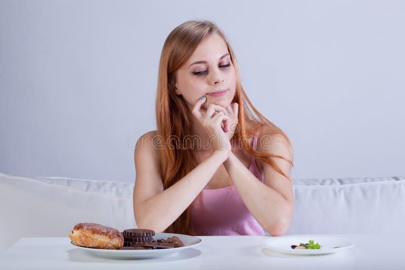 Dziewczyna decyduje co jeść zdjęcia stock